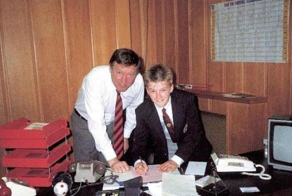 Дэвид Бекхэм подписывает первый контракт с Манчестер Юнайтед. Справа от него Сэр Алекс Фергюссон, 1989 год
