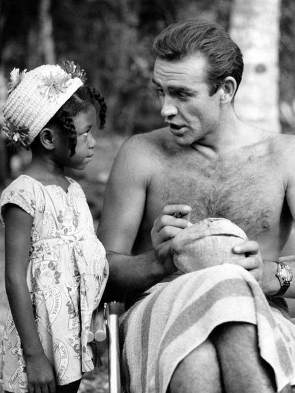 """Шон Коннери подписывает кокос для маленькой фанатки из Ямайки на съемках фильма """"Доктор Ноу"""", 1962 год"""
