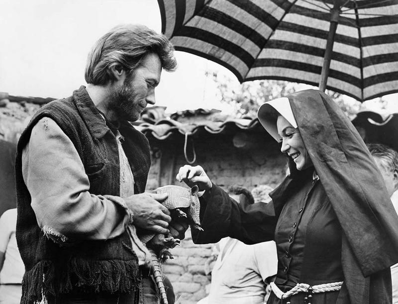 """Клинт Иствуд и Ширли Маклейн играют с броненосцем на съемках фильма """"Два мула для сестры Сары"""", 1969 год"""