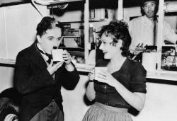 """Чарли Чаплин и Полетт Годдар пьют чай во время перерыва на съемках картины """"Великий диктатор"""", 1940 год"""