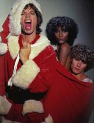 Мик Джаггер в образе Санта-Клауса с Иман Абдулмаджид и Полем ван Равенштейном в качестве подарков, 1977 год