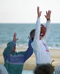 Президент Билл Клинтон не смог поймать мяч во время игры в американский футбол на пляже в отеле Hyatt Regency, 1993 год